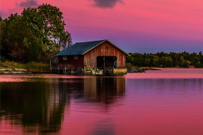 Botenhuis op wateren bij zonsondergang royalty-vrije stock afbeelding