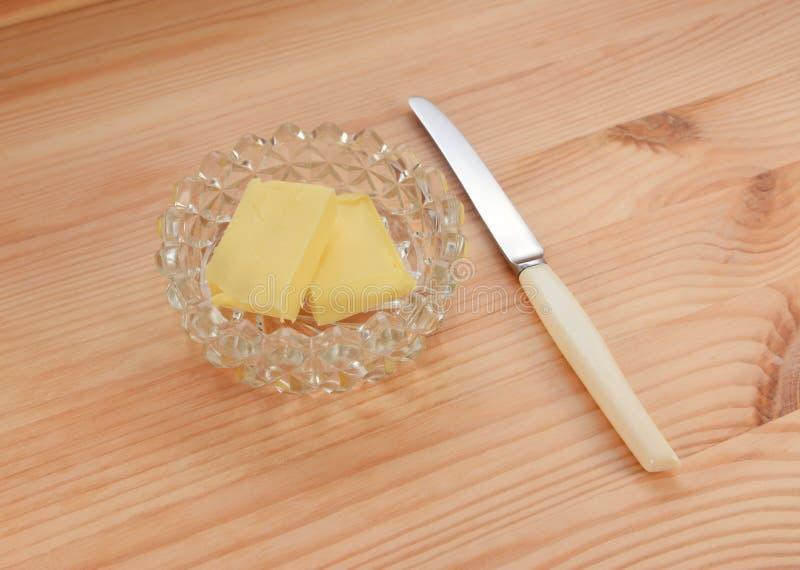 Boter in een glasschotel met een klein mes voor het uitspreiden royalty-vrije stock afbeeldingen