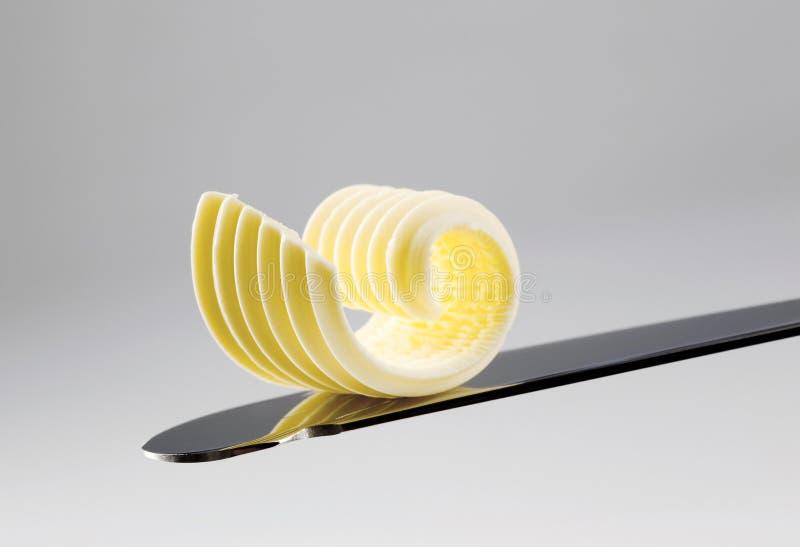Boter krul op een mes stock foto