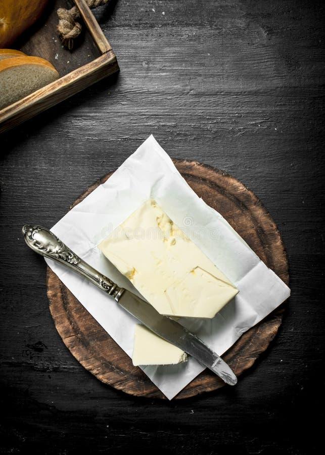 Boter met een mes op de raad royalty-vrije stock fotografie
