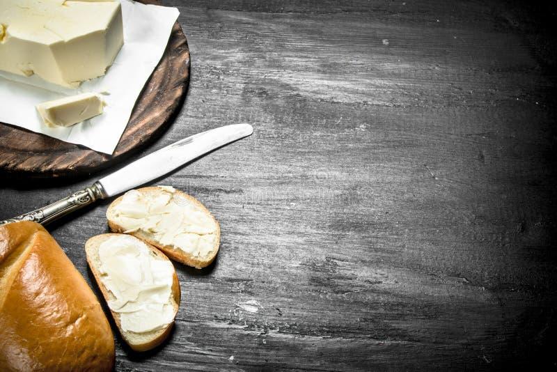 Boter met een mes op de raad stock foto