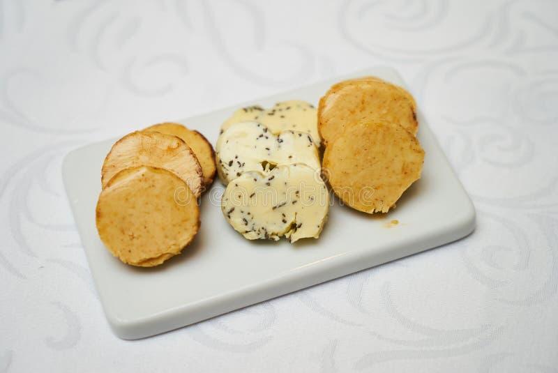 Boter met kruiden en kruiden op ceramische scherpe raad op smaak die wordt gebracht die royalty-vrije stock foto