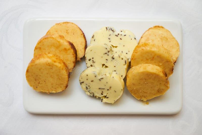 Boter met kruiden en kruiden op ceramische scherpe raad op smaak die wordt gebracht die stock afbeeldingen