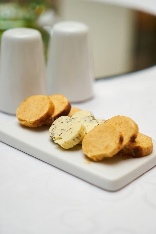 Boter met kruiden en kruiden op ceramische scherpe raad op smaak die wordt gebracht die royalty-vrije stock afbeeldingen
