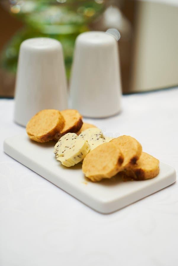 Boter met kruiden en kruiden op ceramische scherpe raad op smaak die wordt gebracht die stock foto