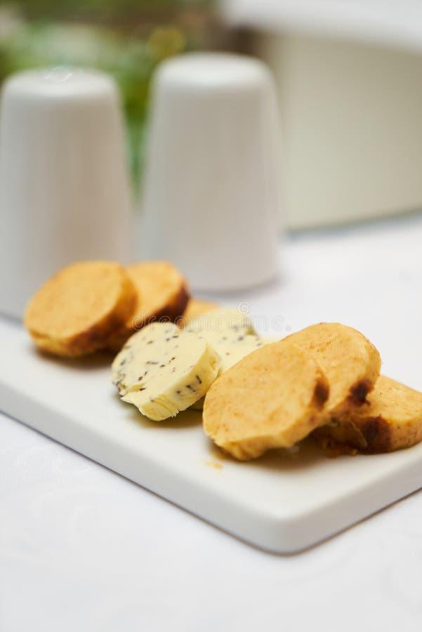 Boter met kruiden en kruiden op ceramische scherpe raad op smaak die wordt gebracht die royalty-vrije stock afbeelding