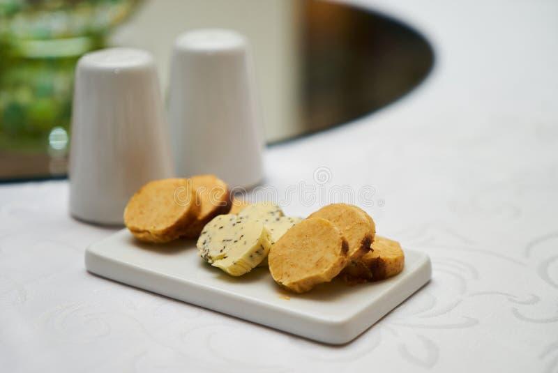 Boter met kruiden en kruiden op ceramische scherpe raad op smaak die wordt gebracht die stock foto's