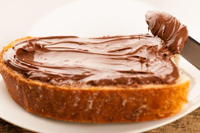 Boterham met zoete die chocoladenoga op houten rug wordt uitgespreid stock foto's