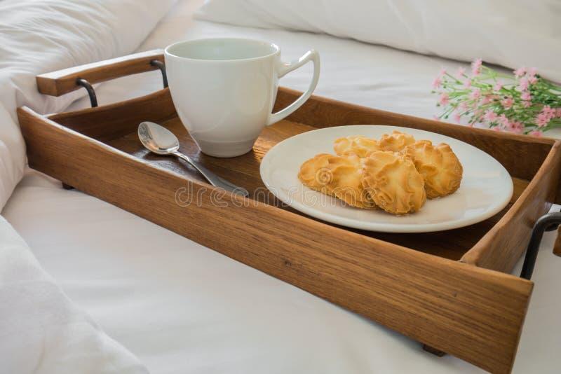 Boterkoekjes en koffiekop in houten dienblad op comfortabel bed royalty-vrije stock foto