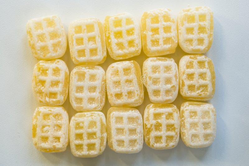 Botersnoepje llamado caramelo holandés 'de la miel de la mantequilla 'del montón contra el fondo blanco imagenes de archivo