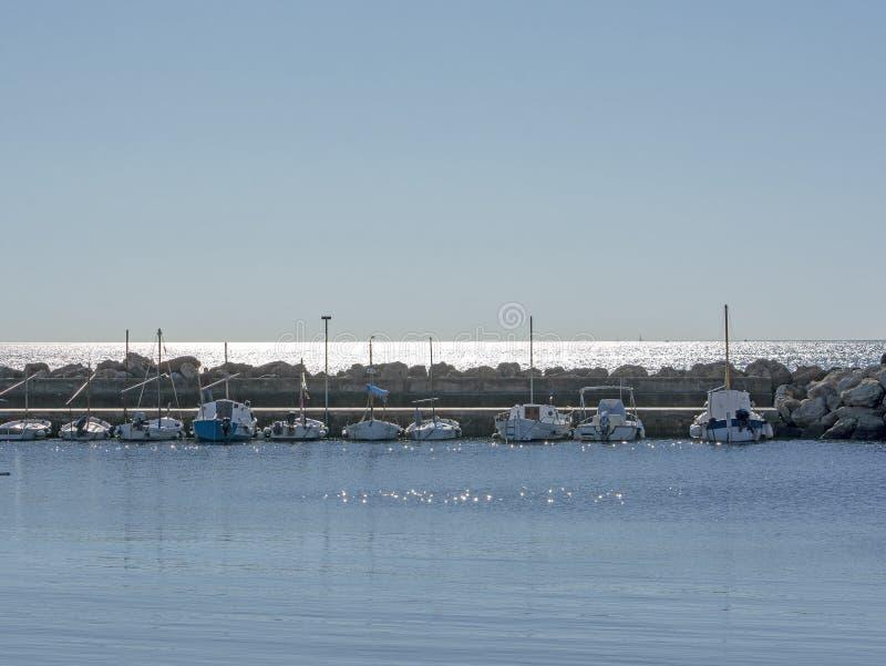 Botes pequeños amarrados en el agua azul tranquila en el embarcadero de Cala Estancia fotos de archivo libres de regalías