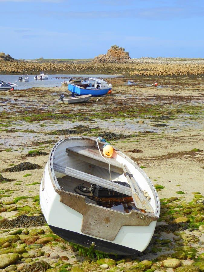 Botes pequeños en la playa durante la bajamar fotografía de archivo