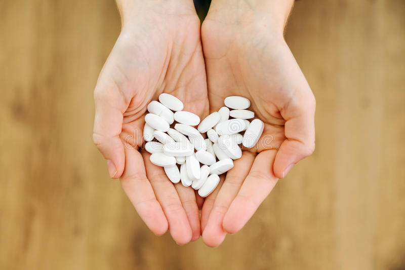 Both hands holding bunch of pills. Overdose or abuse concept. royalty free stock photography