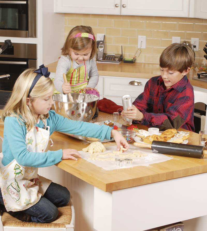 Bother and sisters making cookies royalty free stock photo
