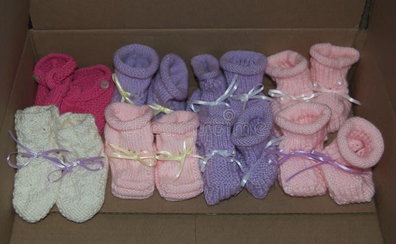 Botines hechos punto del bebé de la muchacha con en fila - colores alineados cintas: Rosa, púrpura, blanco foto de archivo