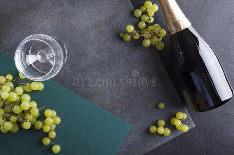 Botle av vin, exponeringsglas och smakliga söta druvor på den lantliga yttersidan arkivfoton