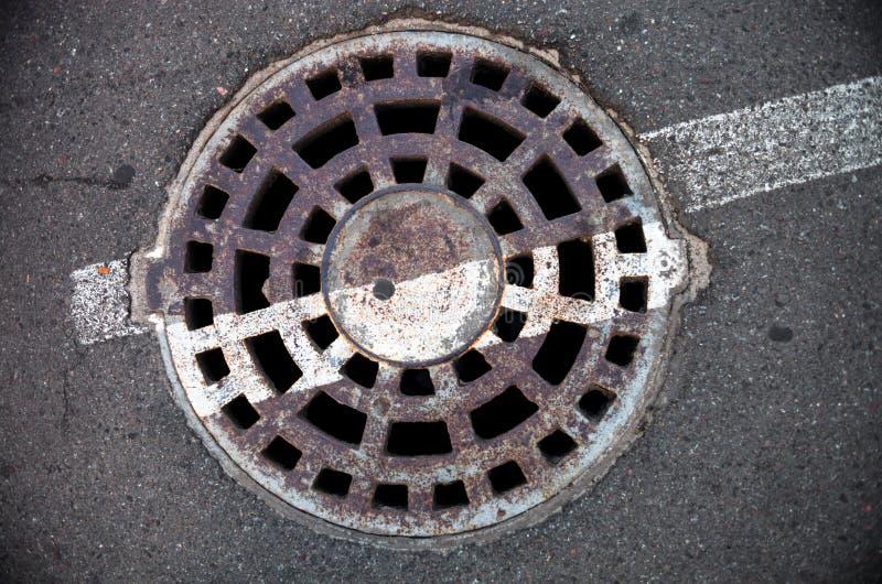 Botola con la copertura del metallo in asfalto con la linea bianca della segnaletica stradale fotografie stock libere da diritti