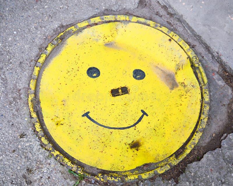 Botola decorativa sotto forma di sorriso giallo Il concetto di progettazione urbana immagini stock libere da diritti