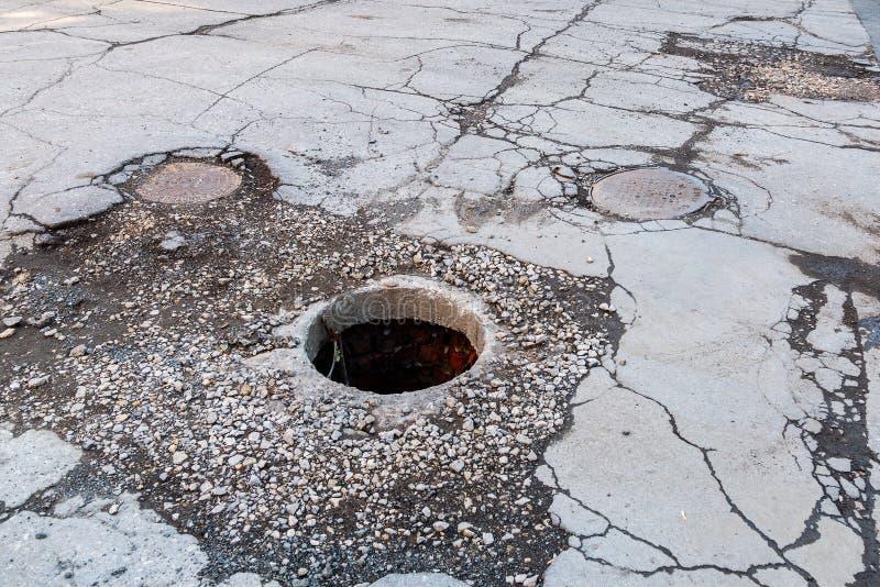 Botola non garantita aperta della fogna sulla strada asfaltata immagine stock