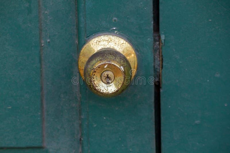 Botones de cobre amarillo viejos en la puerta verde imagenes de archivo