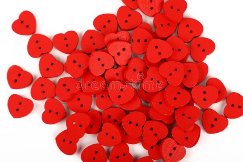 Botones de costura en forma de corazón rojos sobre blanco foto de archivo