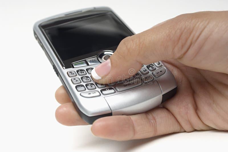 Botones del presionado a mano en el teléfono móvil mientras que mensajería  fotografía de archivo