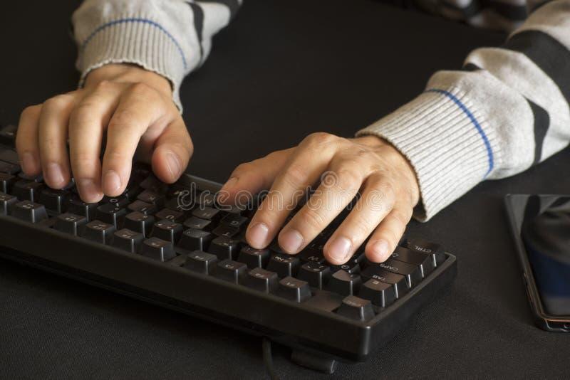 Botones que empujan de las manos masculinas en un teclado fotografía de archivo