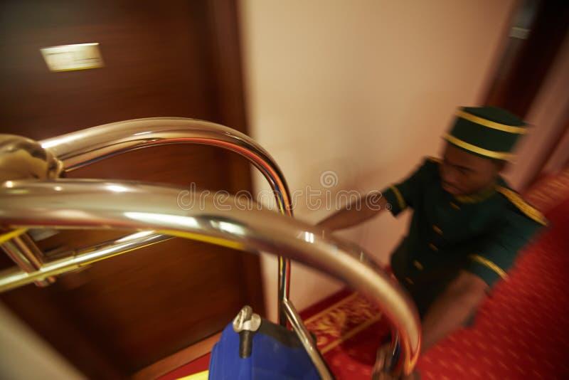 Botones rápido que empuja el carro del equipaje en el hotel Pasillo imagen de archivo libre de regalías