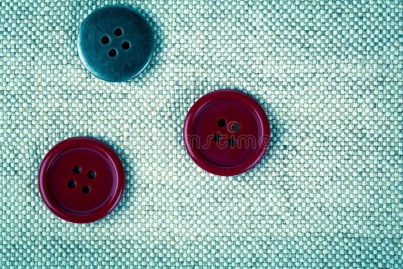 Botones rojos en la ropa vieja imagen de archivo