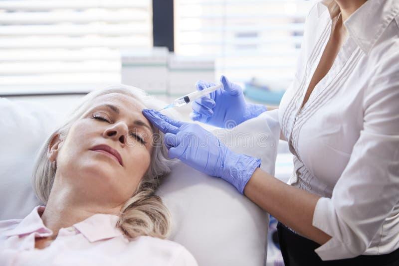 Botox för kosmetologGiving Mature Female patient injektion i panna royaltyfri bild