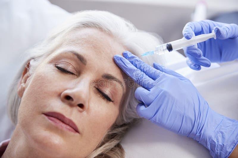 Botox för kosmetologGiving Mature Female patient injektion i panna royaltyfri foto