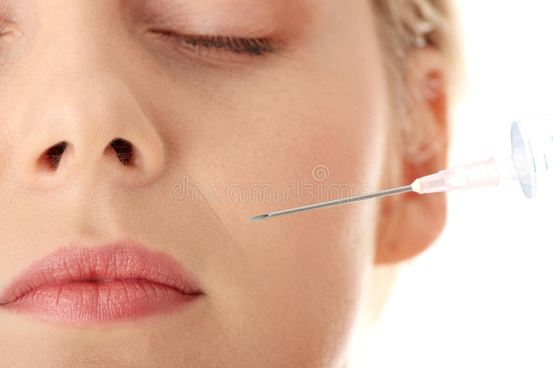 Botox injection. Beautiful woman recieving a botox injection royalty free stock image