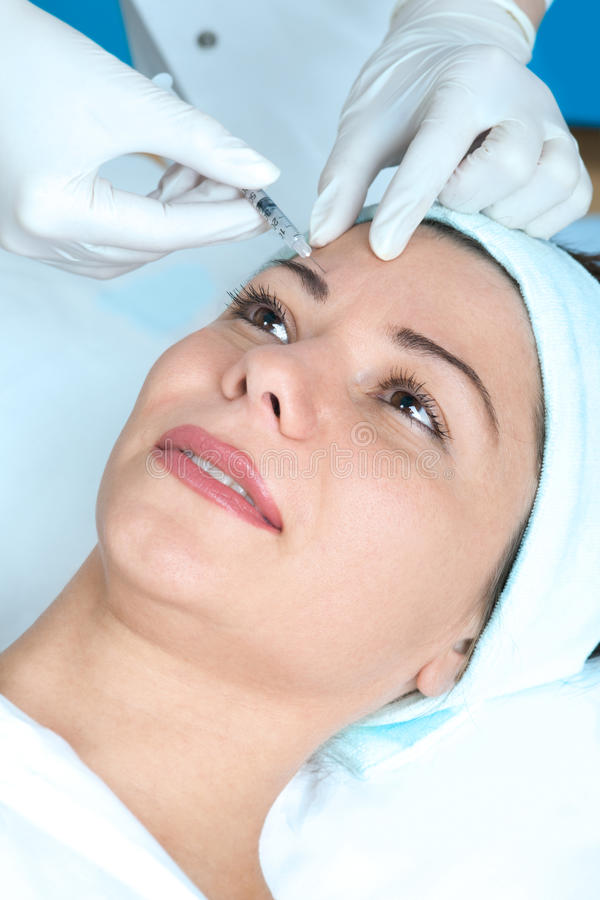 Botox injection. Beautiful woman receiving a botox injection royalty free stock image
