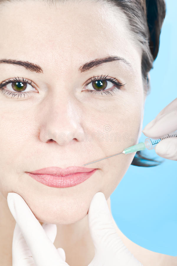 Botox injection. Beautiful woman receiving a botox injection stock image