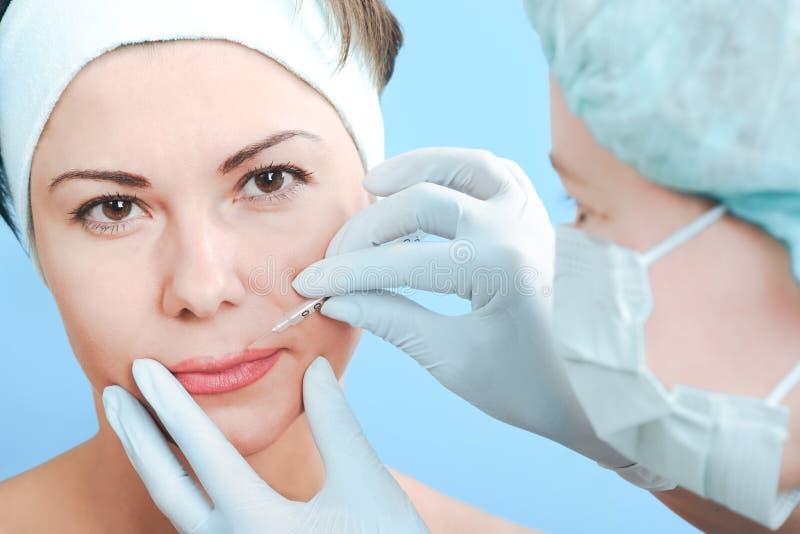 Botox injection. Beautiful woman receiving a botox injection royalty free stock photo