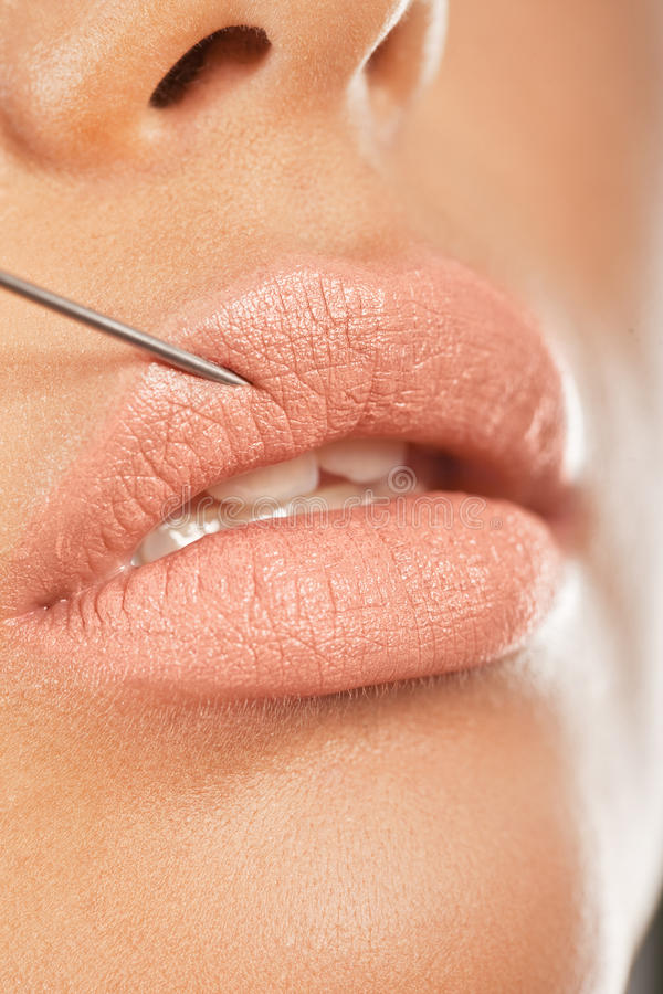 Botox Injection In The Lip. Closeup of a needle giving enhancing botox treatment for fuller lips stock image