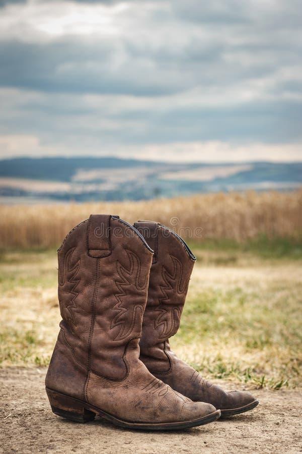 Botte de cowboy dans la scène rurale avec le ciel déprimé images stock
