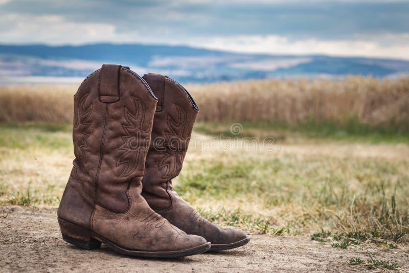 Botte de cowboy dans la scène rurale avec le ciel déprimé photo stock