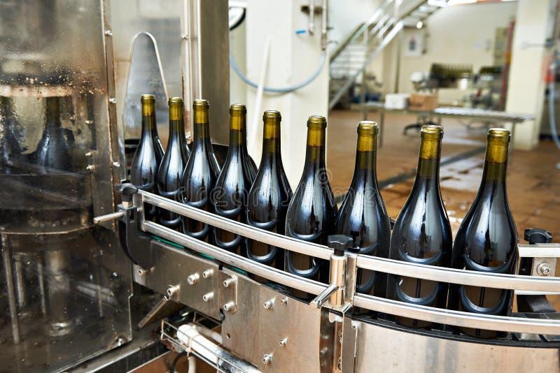 Bottelende en verzegelende transportbandlijn bij wijnfabriek stock fotografie