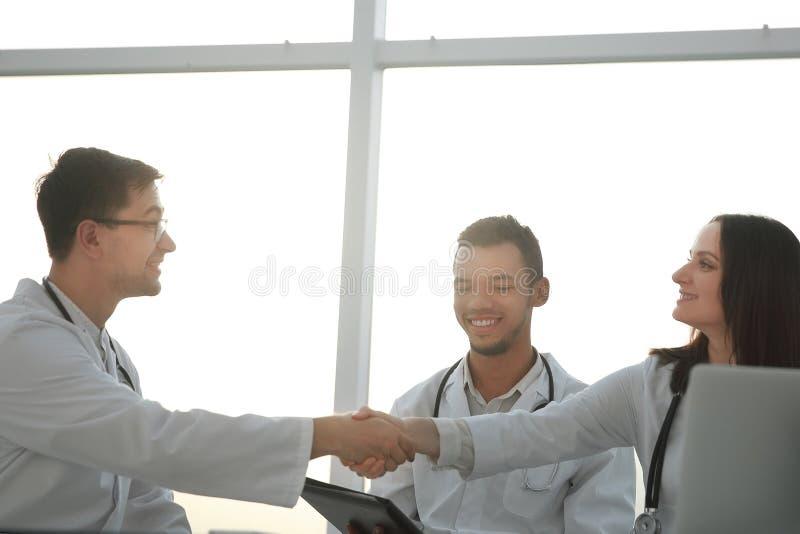 Botten beskådar handskakning av medicinska kollegor på ett möte i kontoret arkivfoton