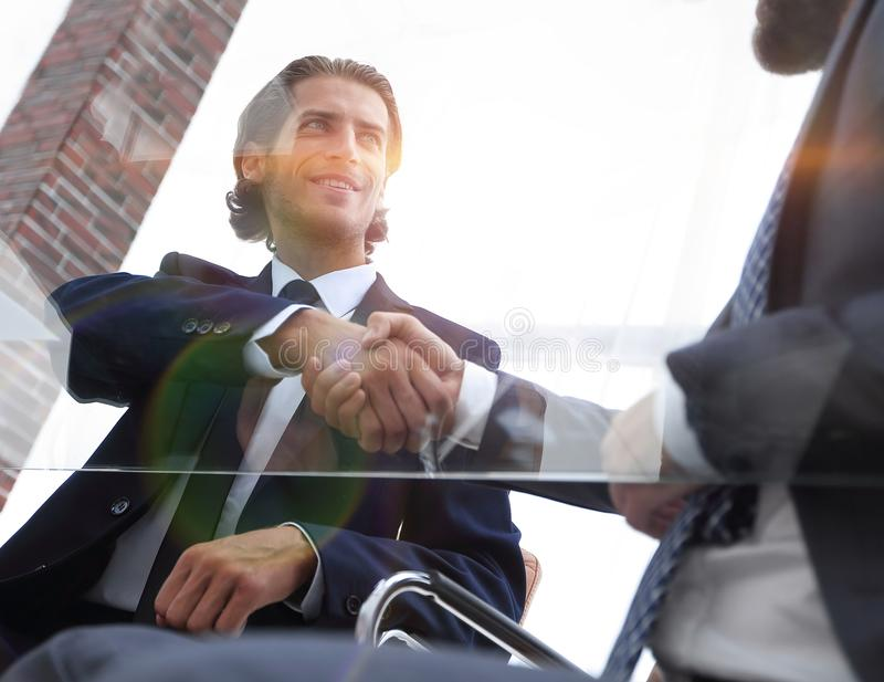 Botten beskådar säker handskakning av affärspartners arkivbilder