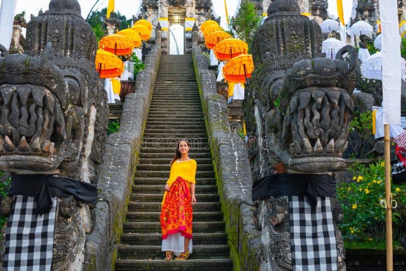 Botten-uppsikt av Balinesetemplet som dekoreras för ferien Galungan Kvinnastandind på trappan bali indonesia close upp arkivbilder