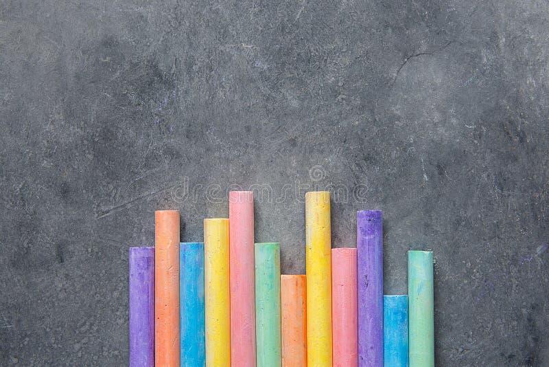 Bottenrader av mångfärgade Chalks på mörk stensvart tavlabakgrund Tillverkar den grafiska designen för affärskreativitet ungeskol arkivbild