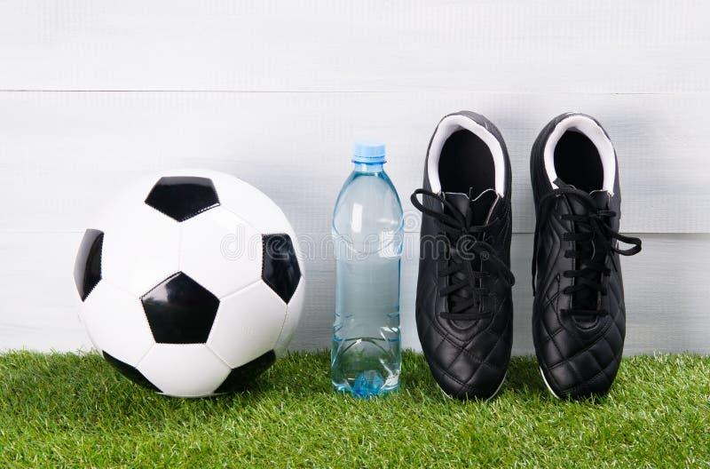 Bottes, ballon de football, une bouteille de l'eau, support sur l'herbe, sur un fond gris, pour le banc photo libre de droits