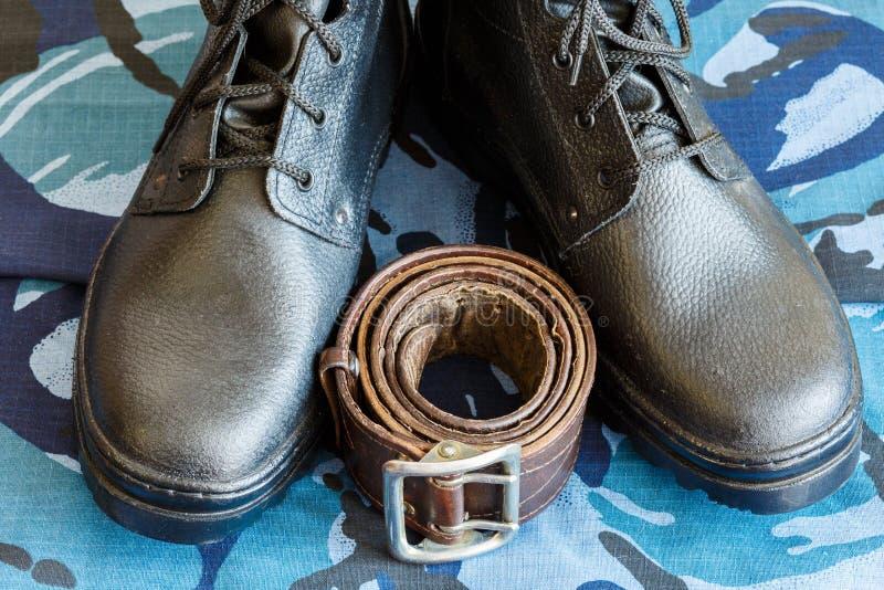 Bottes d'armée et ceinture d'armée sur le tissu bleu de camouflage De façon générale pour le soldat photographie stock libre de droits
