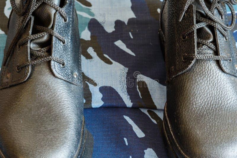 Bottes d'armée et ceinture d'armée sur le tissu bleu de camouflage De façon générale pour le soldat images libres de droits