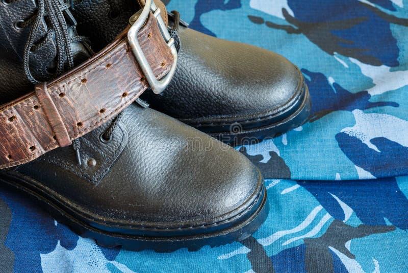 Bottes d'armée et ceinture d'armée sur le tissu bleu de camouflage De façon générale pour le soldat image stock