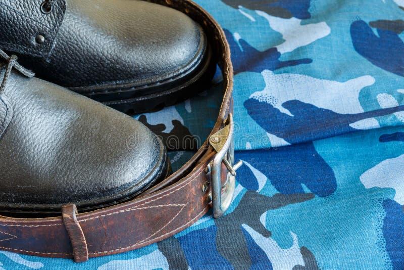 Bottes d'armée et ceinture d'armée sur le tissu bleu de camouflage De façon générale pour le soldat photos stock