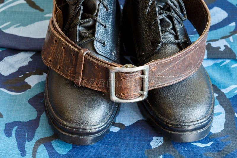 Bottes d'armée et ceinture d'armée sur le tissu bleu de camouflage De façon générale pour le soldat photo libre de droits