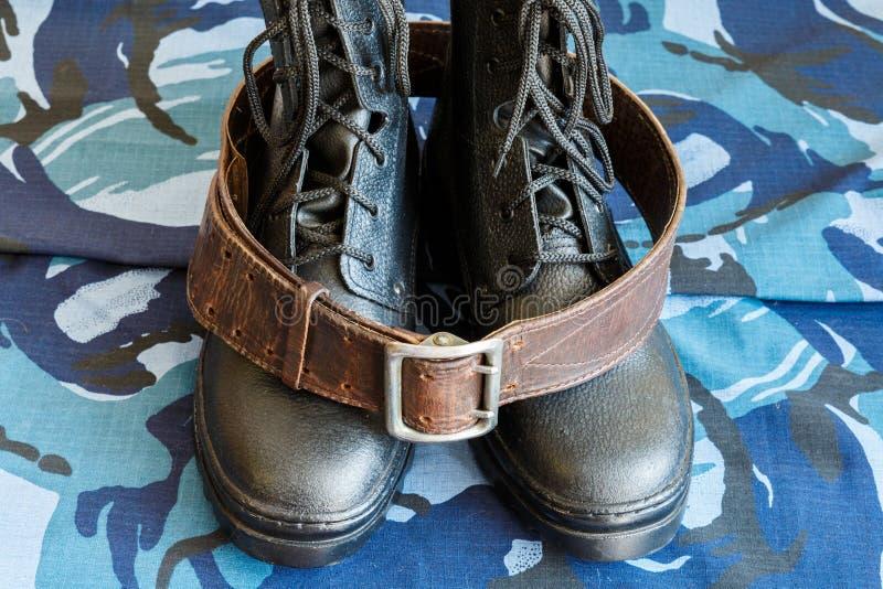 Bottes d'armée et ceinture d'armée sur le tissu bleu de camouflage De façon générale pour le soldat image libre de droits